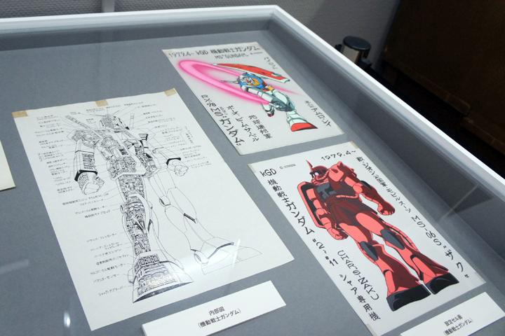 機動戦士ガンダムの設定資料。飯塚氏はアニメ制作の作業量を節約する手段である「バンクシステム」を確立するととともに、アニメの設定などを資料化し体系化、資料図書室化を実現した。この仕組みは現場の作業状況を大幅に改善しただけでなく、ムック本出版などにもつながっていった。