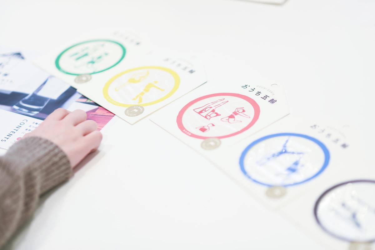 画像:インタビューを受ける金子さんの手元におかれた「おうち五輪」の商品。