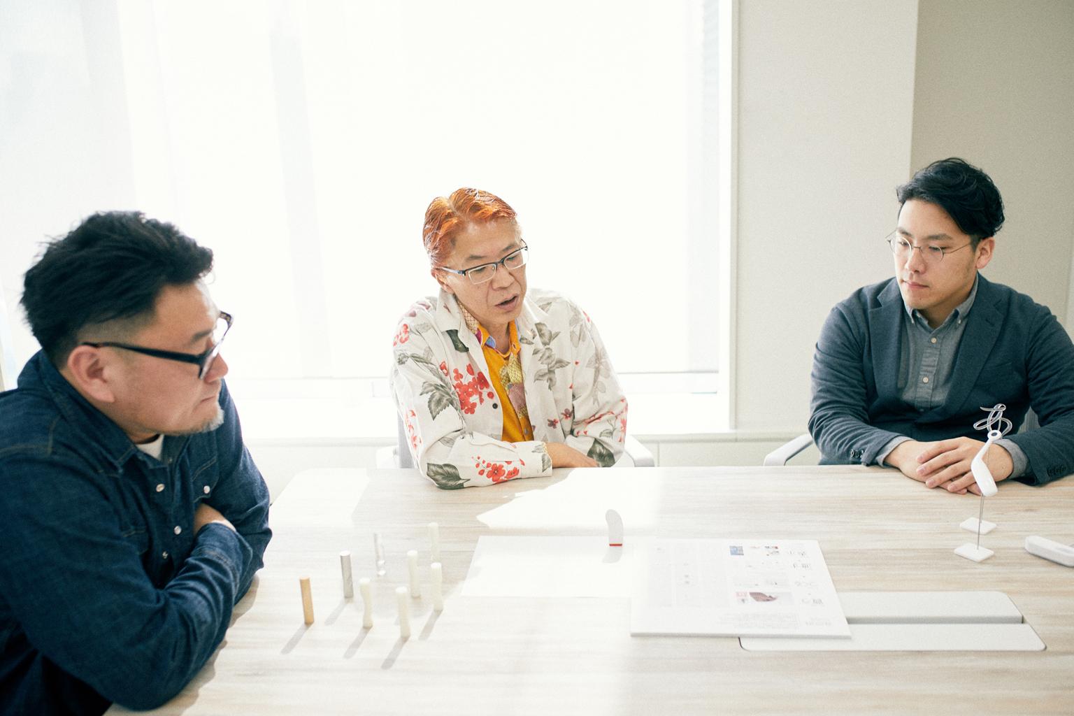 11th『シヤチハタ・ニュープロダクト・デザイン・コンペティション』受賞作品模型を見ながら制作を振り返る、受賞者3名。写真左から明間さん、清水さん、青柳さん。