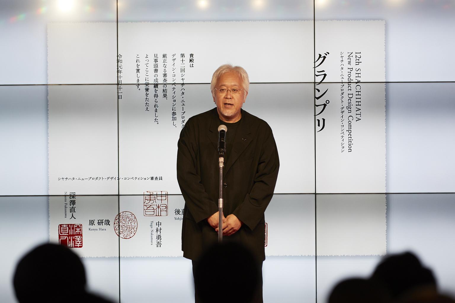 「シヤチハタ・ニュープロダクト・デザイン・コンペティション」表彰状のデザインを壇上で説明する原研哉さん