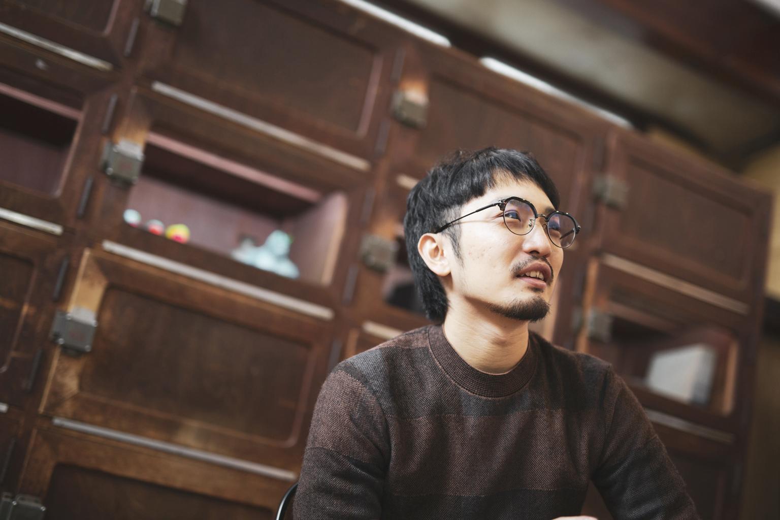 インタビュー中の黒坂祐さん(シェル美術賞2019グランプリ)/背後には作家にスペースをレンタルしている展示棚。もともと銭湯のロッカーだったものを改装した