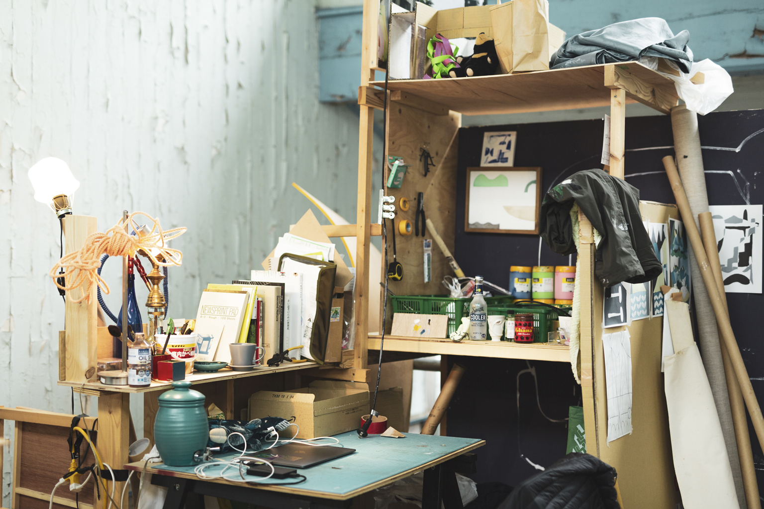木で自作された、黒坂祐さんの棚付き作業机。MacBookが置かれているほか、たくさんの画材や紙が積まれ溢れている。