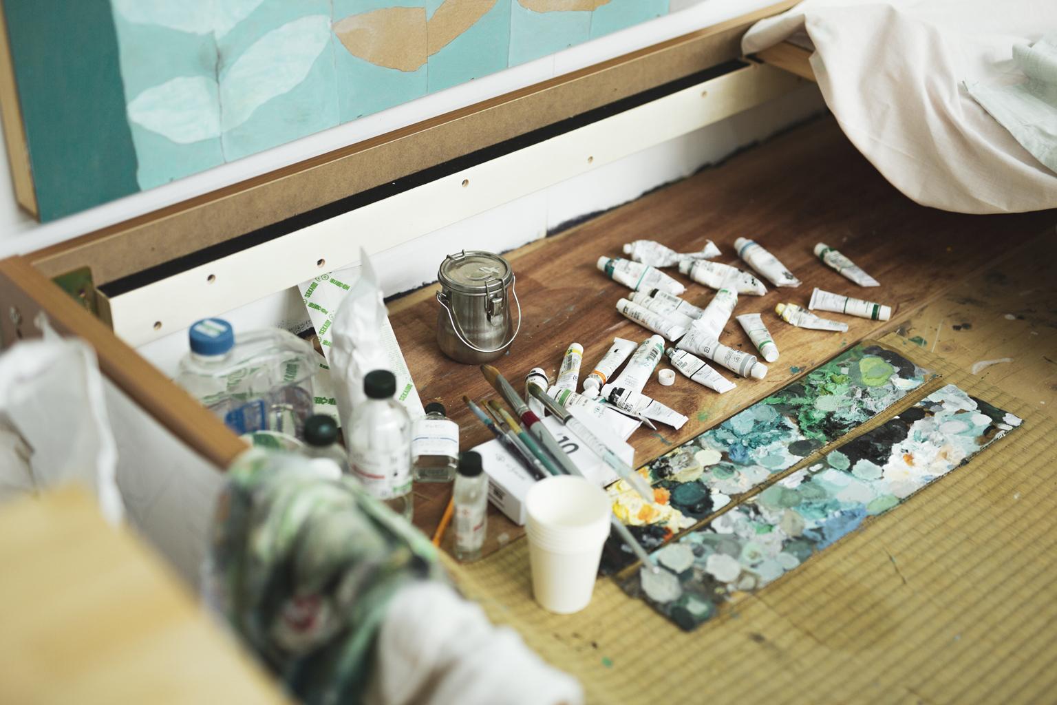 アトリエに散らばった油絵の具のチューブとダンボール製のパレット。パレットには緑~青の落ち着いた色が拡がっている