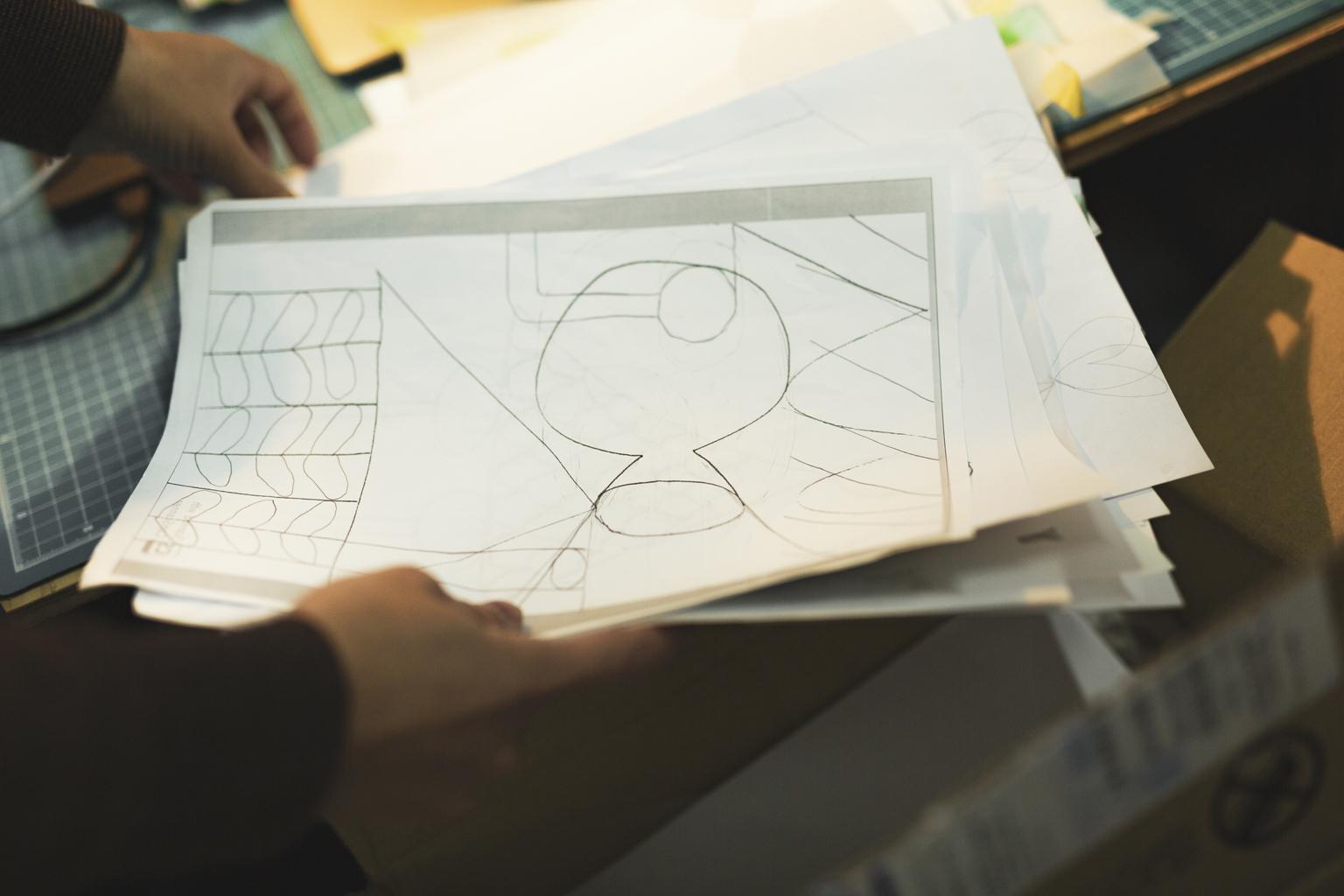 紙に描かれた、たくさんのドローイング(下絵)写真。何枚もの束になっている